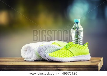 Pair of yellow green sport shoes towel water on wooden board. Accessories for running sport.