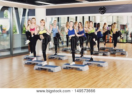 Group of young women in fitness class do step aerobics. Girls at step do leg kicks. Healthy lifestyle at gym studio. Slimming workout
