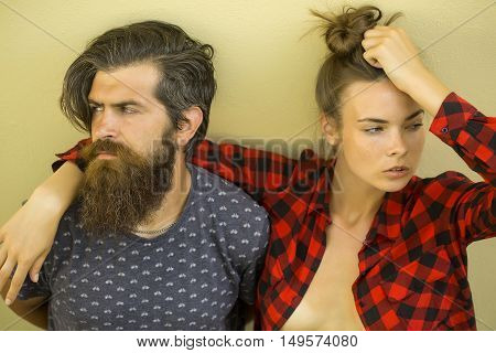 Young sexy couple of pretty woman in checkered shirt and handsome bearded man with long beard outdoor on light background