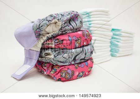 Stacks of disposable diapers and modern cloth diapers together