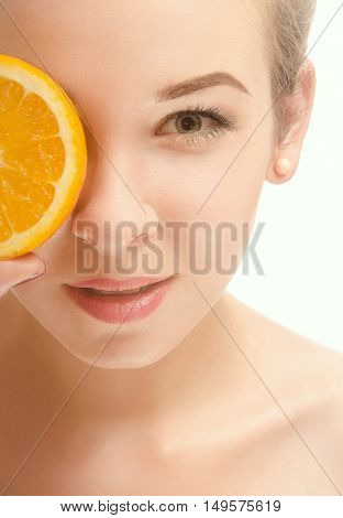 Face of a beautiful young woman who is holding a half of orange slices in front of his eyes and smiling. White background