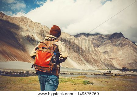 Back of young travel backpacker walking towards the highland mountain.