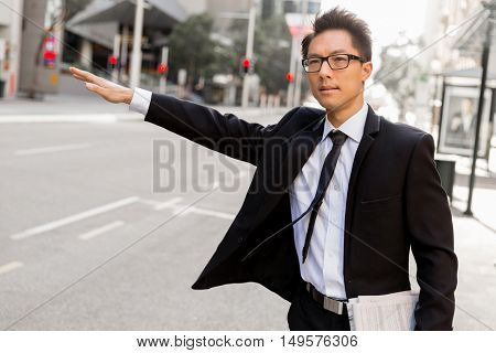 Waving for a taxi in city