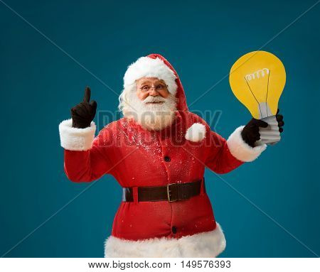 Smiling Santa Claus showing light bulb banner looking happy. Good Santa Claus on blue background having idea