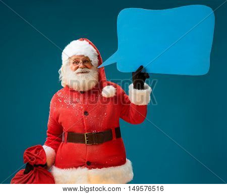 Wise Santa Claus with sack of gifts showing sign speech bubble banner looking happy excited. Happy Santa Claus on blue background having idea