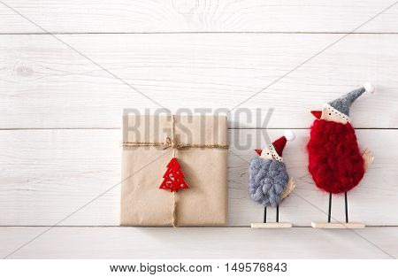 Christmas background with copy space. Top view of gift boxes and funny birds toys. Presents in craft paper with red ribbon bows and spruce tree on white wood. Celebration of winter holidays concept
