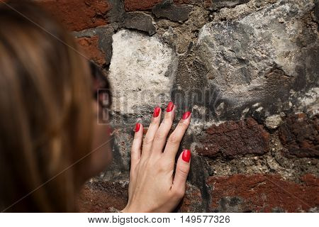 Woman touches the palm of the old wall close up