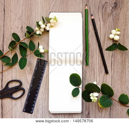 Closeup of notebook and stationery on wooden background decorated with green snowberry branches. School or university supplies. Top view flat lay view from above