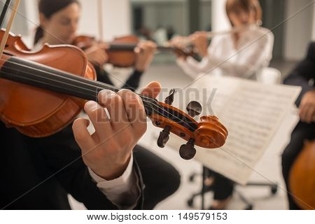 Confident violinist playing his instrument and reading a music sheet classical music symphony orchestra performing on background