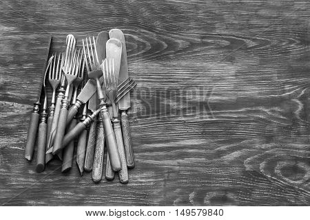 Old cutlery on a wooden table. Texture background