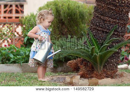 Diligent Pretty Little Girl Watering Flowers In Summer Garden.