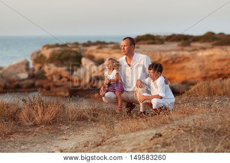 Portrait of cheerful happy father son and small daughter on background of sea Spain