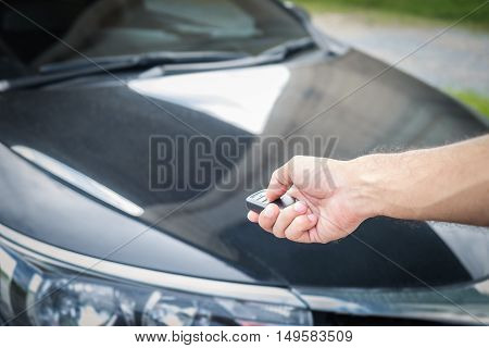 Young man opening his car door with the control remote key.