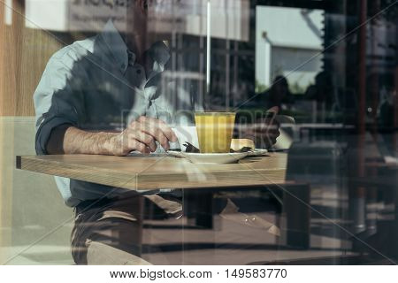 Man having breakfast at the cafe next to a window with reflections