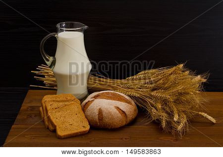 Pitcher of milk round rye bread a sheaf of wheat bread slices on a wooden table