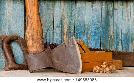 Carpenter tools: ax planer and saw on the background of the old wooden walls