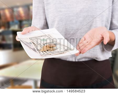 Waitress hand holding tray money change giving back to customers in cafe.
