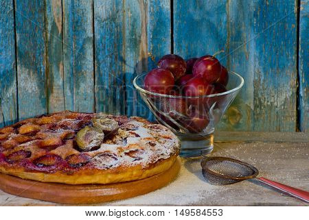 Plum cake with powdered sugar strainer piala with plums old wooden background
