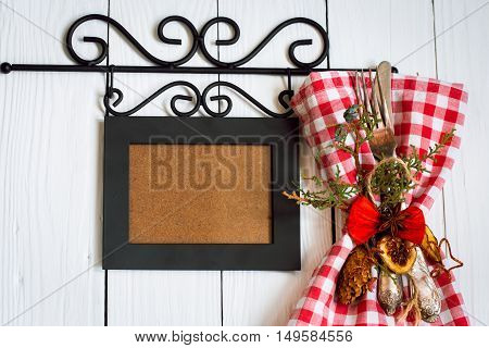Beautiful Christmas Cutlery on a napkin in red and white ornaments on white wooden background.Place for text in photo frame.