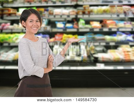 Smiling woman employee standing in supermarket shelf for your advertising