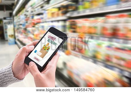Hand holding smartphone with delivery service app on screen and fresh food supermarket store background