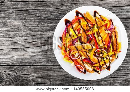 mango bread crumbed chicken meat peanuts bell pepper red onion salad on white dish with balsamic vinegar dressing on old planks blank space left view from above