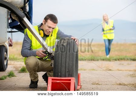 Technician fixing airplane's wheel before flight at airport