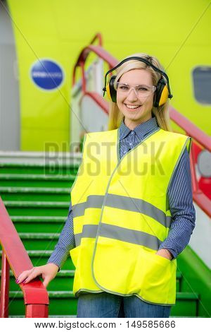Aircraft engineer with CB radio standing in front of a commercial airliner