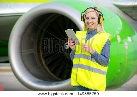 Aircraft engineer with a checklist in his tablet