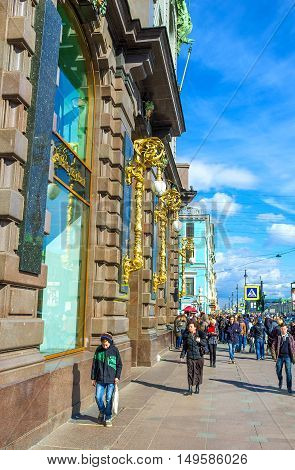 SAINT PETERSBURG RUSSIA - APRIL 25 2015: The walk along the crowded Nevsky Prospekt at the stone wall of Singer House widely known as the House of Books on April 25 in Saint Petersburg.