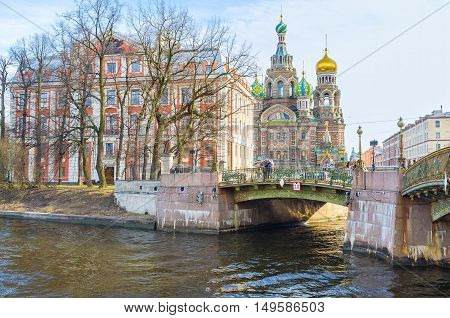 SAINT PETERSBURG RUSSIA - APRIL 25 2015: The bright red building of the Folk Arts State Higher School at the Moyka River hides the Church of the Savior on Spilled Blood on April 25 in Saint Petersburg.