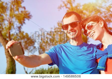 couple tourists  walking in the park and take selfie