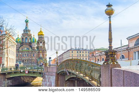 SAINT PETERSBURG, RUSSIA - APRIL 25, 2015: The scenic old fashioned streetlight on Malokonushenny bridge with the Church on Spilled Blood on the background, on April 25 in Saint Petersburg.
