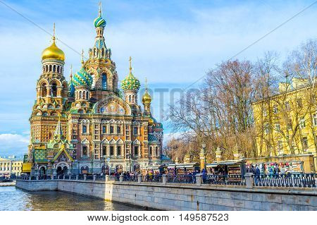 SAINT PETERSBURG RUSSIA - APRIL 25 2015: The crowded souvenir market on the Griboedov Canal embankment at the Church of the Savior on Spilled Blood on April 25 in Saint Petersburg.