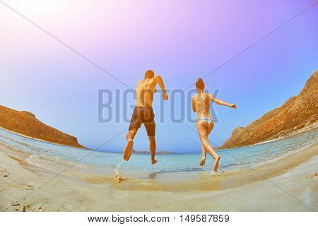couple running in the sea beach on a blue sky background