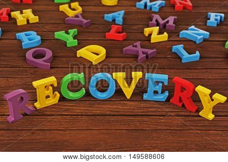 Word RECOVERY made of colourful letters on wooden background