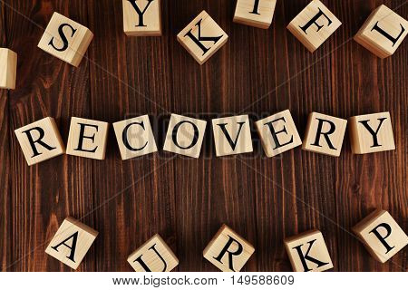 Medical concept. Word RECOVERY made of cubes with letters on wooden background