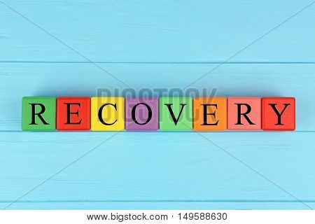 Word RECOVERY made of colourful cubes with letters on blue wooden background
