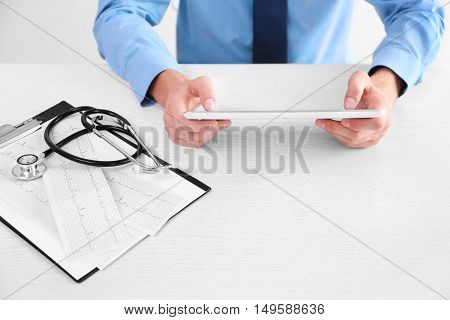 Stethoscope, cardiogram and clipboard on doctor table, close up view