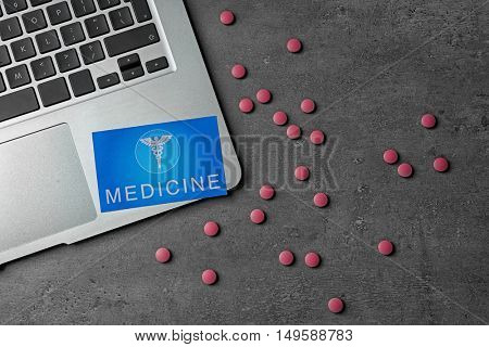 Medical service concept. Visiting card, pills and laptop on grey background