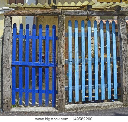 Two old blue picket gates in the coastal north east Italian town of Marano Lagunare in Friuli Venezia Giulia.