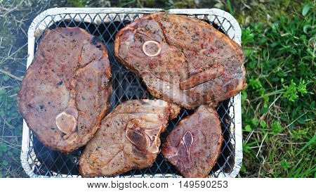 Lamb steaks cooking on disposable grill Iceland