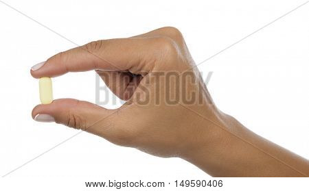 Pill in between the fingers of a woman isolated on white background.