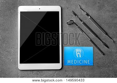 Medical service concept. Visiting card, dental equipment and tablet on grey background