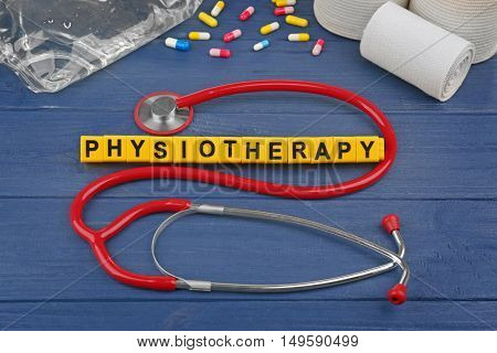 Medical concept. Medical equipment and word Physiotherapy on blue  wooden background
