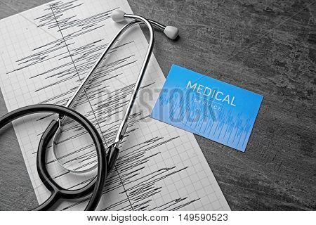 Medical concept. Stethoscope, business card and ECG chart on gray background