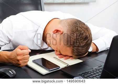 Angry young businessman lying on his desk