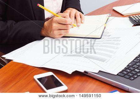 Woman Holds A Pencil And Writes Something
