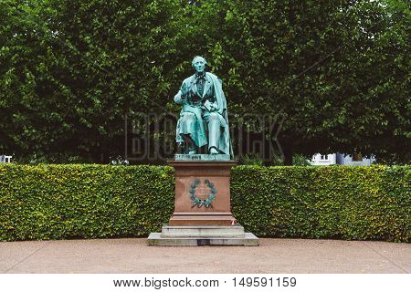 Copenhagen, Denmark - September, 22th, 2015. Hans Christian Andersen statue in Rosenborg garden. Bronze sculpture of famous danish fairy tale writer amid green plants.