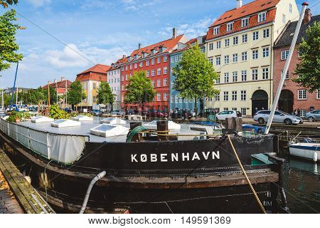September, 24th, 2015 - Copenhagen, Denmark. Christianshavn harbor with colorful scandinavian houses and private Kobenhavn barge on the water of canal.